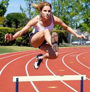 woman jumping hurdles