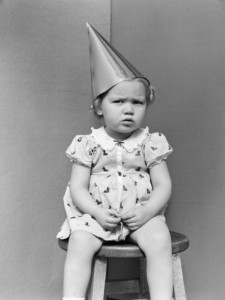 h-armstrong-roberts-girl-wearing-dunce-cap-sitting-on-stool-in-corner